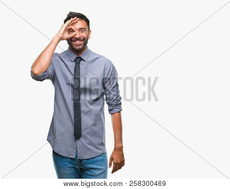 Adult hispanic business man over isolated background doing ok gesture with hand smiling, eye looking through fingers with happy face.