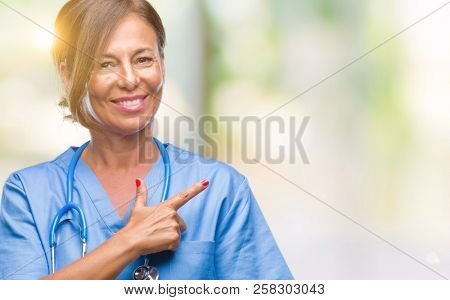 Middle age senior nurse doctor woman over isolated background cheerful with a smile of face pointing with hand and finger up to the side with happy and natural expression on face looking at the camera