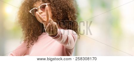 African american woman wearing pink sunglasses smiling looking to the camera showing fingers doing victory sign. Number two.