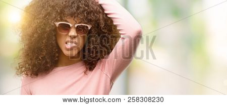 African american woman wearing pink sunglasses confuse and wonder about question. Uncertain with doubt, thinking with hand on head. Pensive concept.