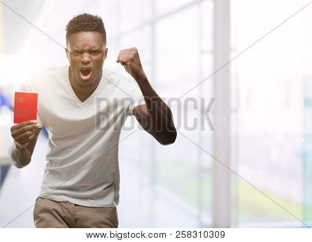 Young african american man holding passport of Switzerland annoyed and frustrated shouting with anger, crazy and yelling with raised hand, anger concept
