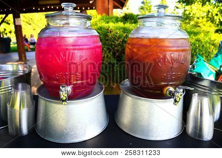 Jugs of cold huckleberry lemonade and iced tea on galvanized aluminum tubs displayed at an outdoor event
