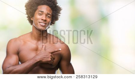 Afro american shirtless man showing nude body over isolated background cheerful with a smile of face pointing with hand and finger up to the side with happy and natural expression on face