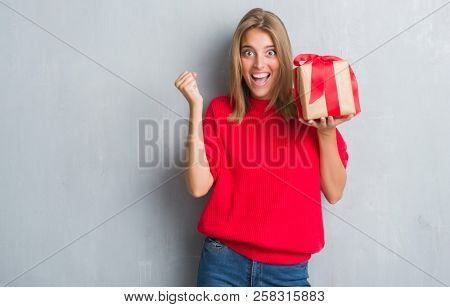 Beautiful young woman over grunge grey wall holding in love a present screaming proud and celebrating victory and success very excited, cheering emotion