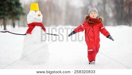 Little Boy Playing With Funny Snowman. Active Outdoors Leisure With Children In Winter. Kid During S