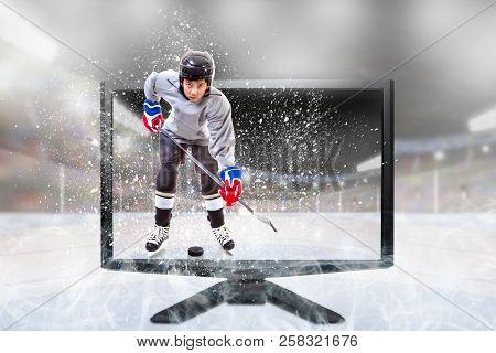 Junior Ice Hockey Player In Competitive Sports Gear Standing Inside Brightly Lit Outdoor Stadium On