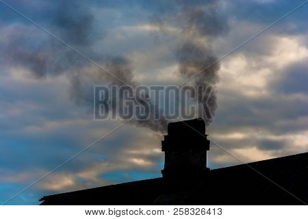 Two Jets Of Black Smoke From A Chimney Over A Cloudy Sky.