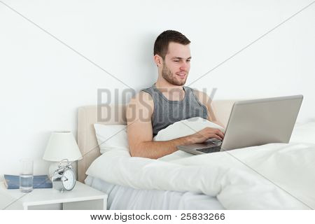 Calm man using a laptop in his bedroom