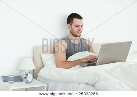 Rustige man met een laptop in zijn slaapkamer