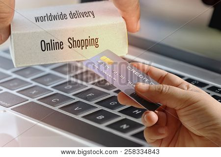 The Word Online Shopping And Worldwide Delivery, Text On Cardboard Box, And Hand Holding Of Mock Up