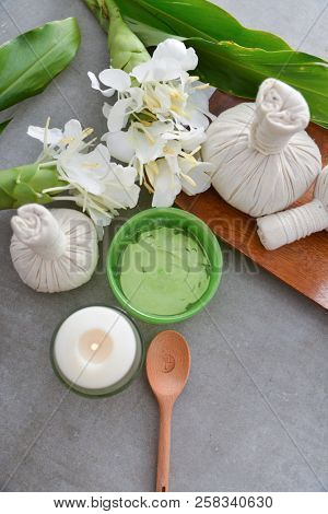 Spa setting with ginger flower , herbal, ball ,candle, soap, spoon, bowl,oil on gray background