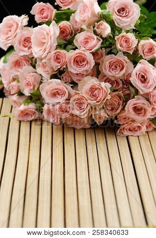 pink branch rose on bamboo board mat background