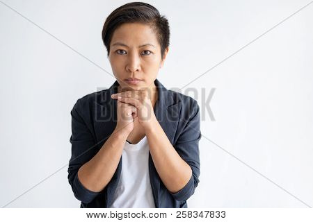 Focused Asian Woman Holding Hands Together. Young Lady Looking At Camera. Contemplation Concept. Iso