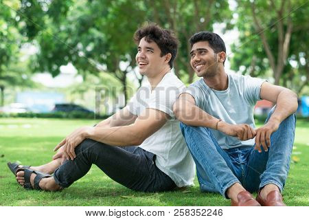 Excited Handsome Young Men In Casual Clothing Sitting On Grass In City Park. Cheerful Dreamy Carefre