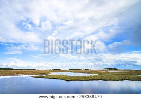 River Landscape With Dry Plains Under A Blue Sky In The Summer