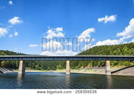 Large Bridge Over A Lake Near A Forest In The Summertime With Blue Sky