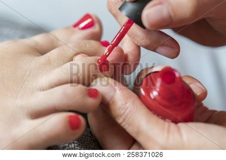 The Master Covers The Customer's Nails With Varnish. Hands In Gloves Cares About A Woman's Foot Nail