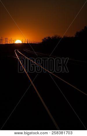 Railroad Tracks Lit During A Golden Summer Sunset