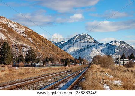 Railroad Tracks Leading To Snowy Mountain Scene