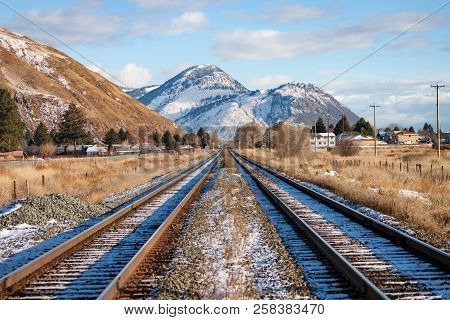 Two Tracks Leading To Mountains In Winter