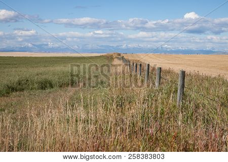 Wooden Fence Leading To Mountains And Prairie Sky