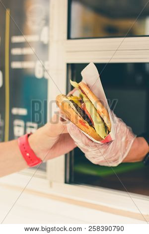 Street Sale And People Concept - Happy Seller Giving Burger To Customer At Food Truck