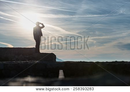 Businessperson In A Suit Standing Outdoors On A Wall Against A Sunrise.