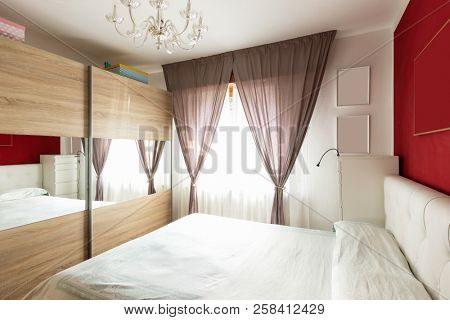 Double bedroom with wardrobe and curtains. Nobody inside