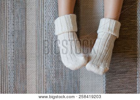 Legs Of Little Child Girl Is In Woolen Knitted Socks. Kid Is Sitting On Warm Floor With Carpet And H