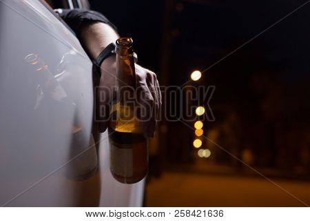 Drunk Young Man Driving A Car With A Bottle Of Beer. Don't Drink And Drive Concept. Driving Under Th