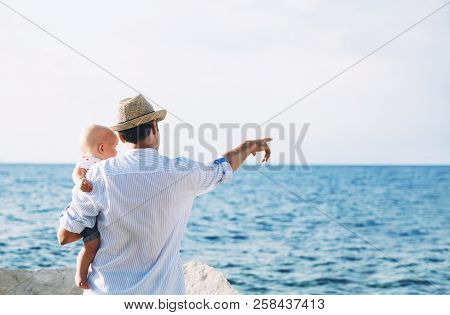 Father With Daughter On Sea And Sky Backgrounds. Man And Baby Are Point Out Forward. Parent And Chil