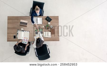 Top View Of Business People Shaking Hands After Sealing A Deal. High Angle View Of Casual Businesswo