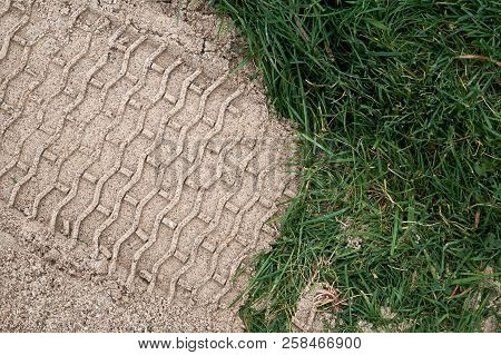 Tire Tracks In The Sand That Was Placed Over The Green Grass During Construction.
