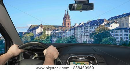 Driving A Car In The City Centre Of Basel, With Its Famous Red Sandstone Cathedral, Switzerland