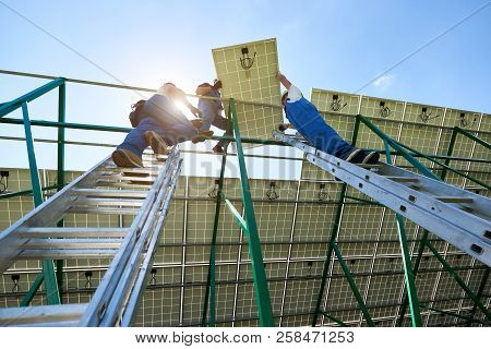 Professional Workers Team Installing Solar Panels On The Green Metal Construction Using Different Eq