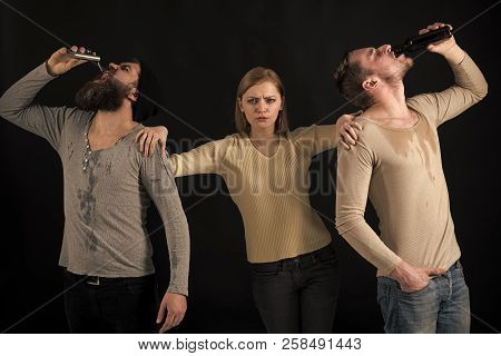 Bad company, destructive, harmful habits. Dirty men drink alcohol out of flask and bottle, dark background. Bad influence concept. Woman on pensive face stands between two alcohol addicted men poster