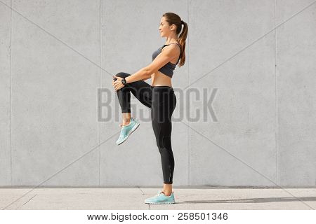 Shot Of Flexible Young Woman Warms Up Before Jogging On Stadium, Wears Sportsclothes, Shows Her Stom