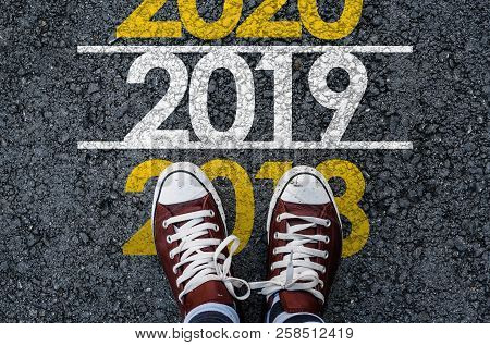Happy New Year 2019. Man Legs In Sneakers Standing On Asphalt Road And Number 2018 Next To Number 20