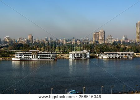 Nile River On Its Way Through The City Of Cairo, Egypt With Boats Moored On The Shore And View Of Mo