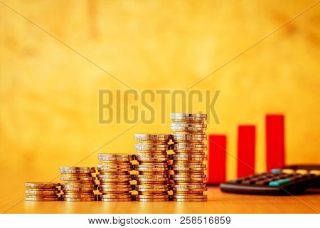 Stacking Gold Coins And Red Arrow Graph With Growing Value Calculator Put On The Desk