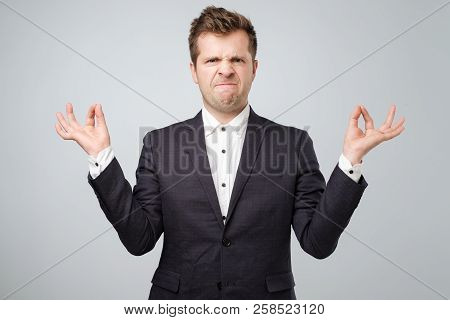 Studio Portrait Of Young Handsome Male In Suit, In Meditation Pose, Trying To Calm Down In Zen, But