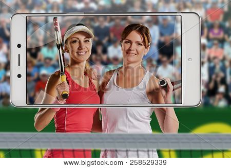 Successful Sportswomen With Racket At The Tennis Court, Background Are With Court And Fans With Tenn