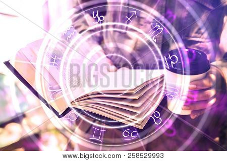 Close Up Of Hands Holding Abstract Book With Zodiac Wheel. Magic And Astrology Concept. Double Expos