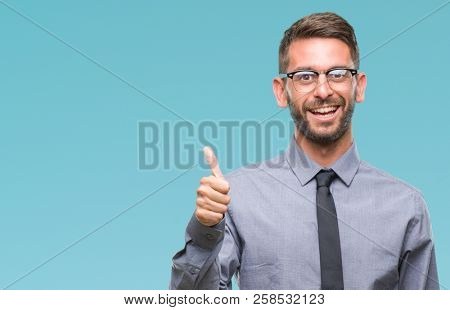 Young handsome business man over isolated background doing happy thumbs up gesture with hand. Approving expression looking at the camera with showing success.