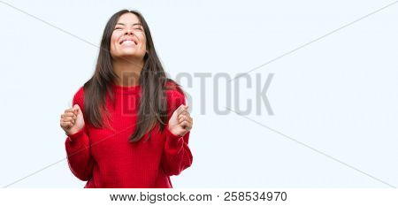Young beautiful hispanic wearing red sweater excited for success with arms raised celebrating victory smiling. Winner concept.