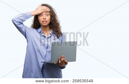 Young hispanic woman holding computer laptop stressed with hand on head, shocked with shame and surprise face, angry and frustrated. Fear and upset for mistake.