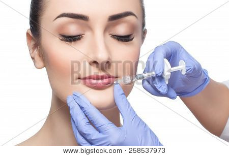 poster of The cosmetologist makes injections of botulinum toxin in the lips of the patient. Cosmetology skin care.