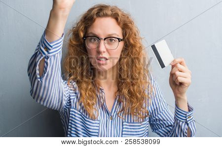 Young redhead woman over grey grunge wall holding credit card annoyed and frustrated shouting with anger, crazy and yelling with raised hand, anger concept
