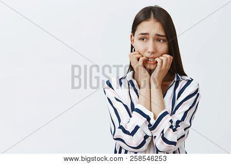 Girl witnessed crime, feeling anxious and afraid. Portrait of innocent gloomy and nervous female in trendy clothes, biting fingernails, frowning and gazing aside, being confused and scared poster
