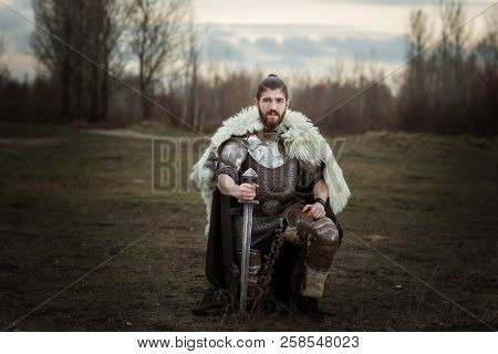 Knight In Armor With A Sword In Hand, Standing On One Knee.